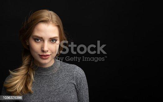istock portrait of blonde girl on dark background 1036325386