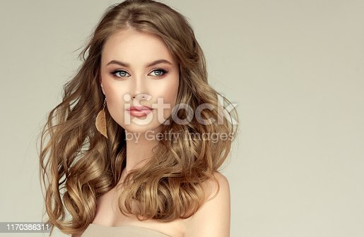 Young, blonde haired woman  with voluminous hair. Model with long, dense, freely laying hairstyle and neat makeup, leaf shaped golden earrings dressed in her ears. Perfect dense, wavy deep blonde hair. Soft look aside.