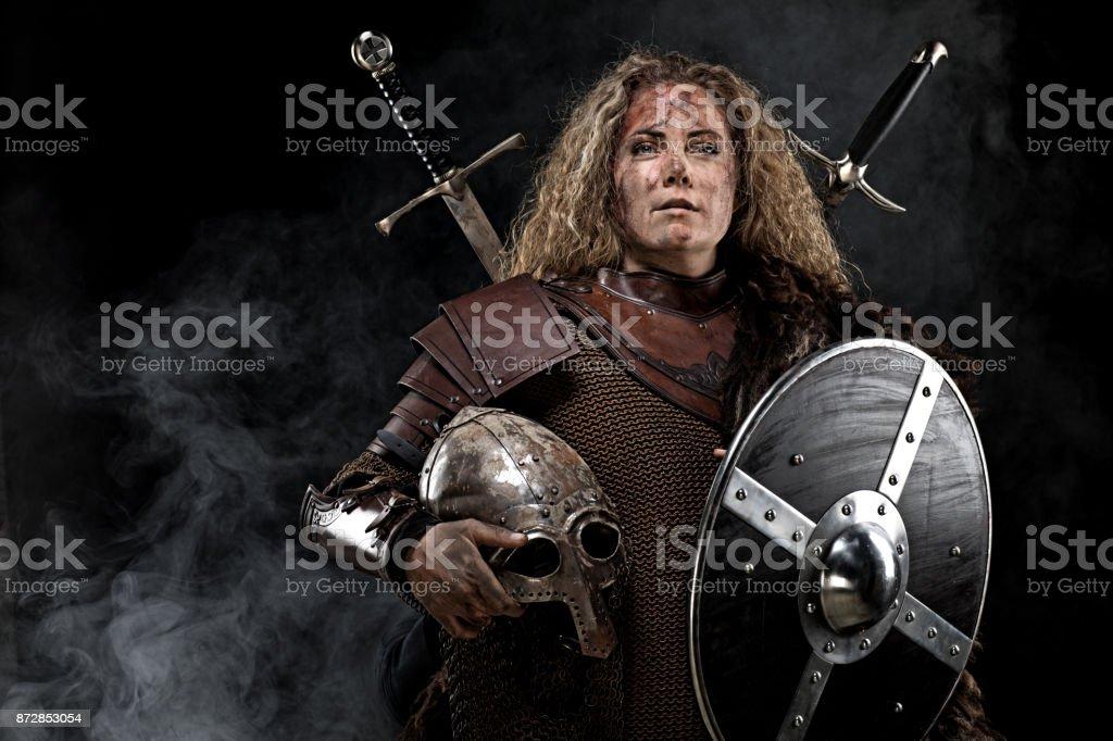 Portrait of blonde viking warrior female holding a sword in studio shot stock photo