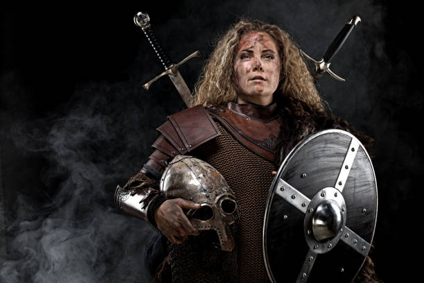 portrait of blonde viking warrior female holding a sword in studio shot - indumento corazzato foto e immagini stock
