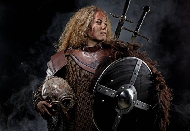 portrait of blonde viking warrior female holding a sword in studio shot - tarcza broń zdjęcia i obrazy z banku zdjęć