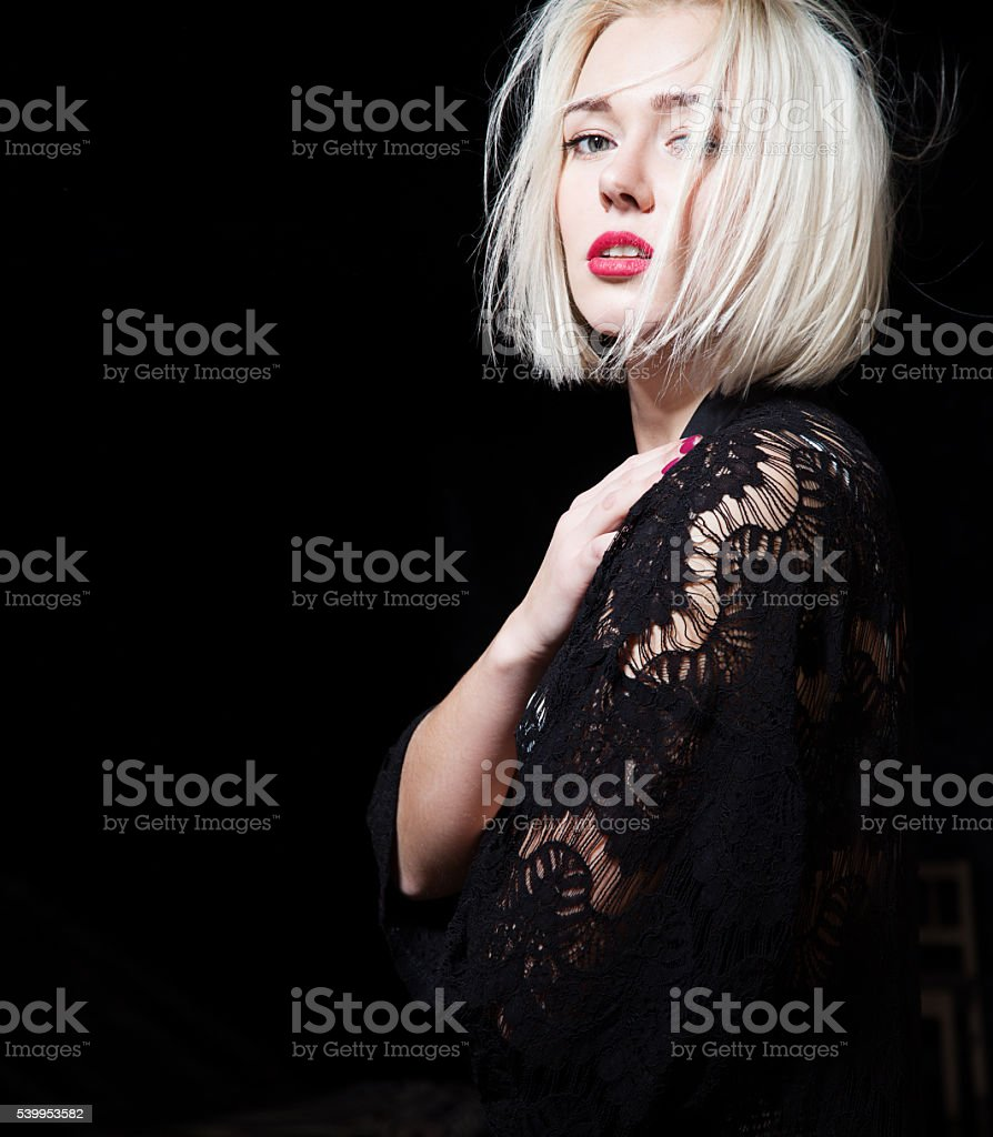 Portrait of blonde with short hair in a black dress stock photo