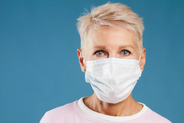 Portrait of blond-haired female doctor in medical mask for protection of infections standing against blue background stock photo