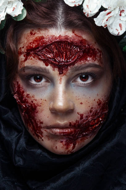 Portrait of bloody horrible scary zombie girl in a Halloween festive makeup. Red eyes. stock photo