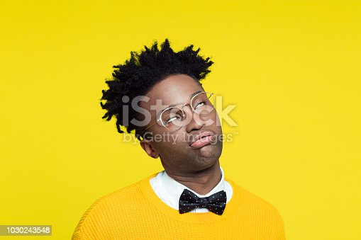 Portrait of tired nerdy young afro american man wearing yellow sweater and black bow tie standing against yellow background.