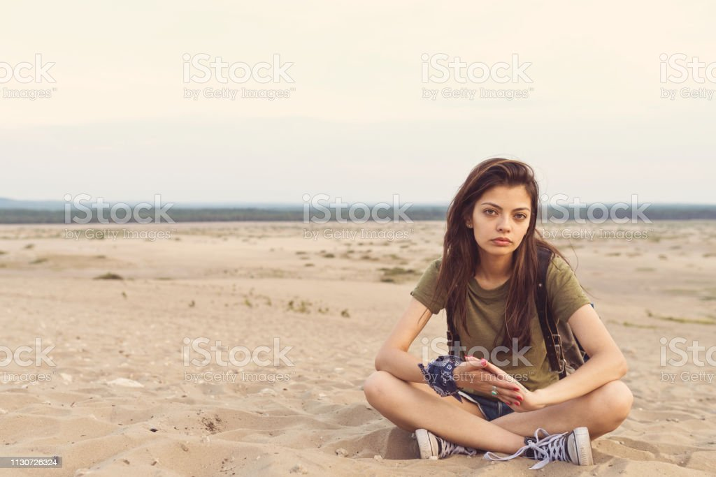 Portrait of bored hiker sitting on sand in desert Portrait of beautiful hiker sitting on sand. Bored young woman is relaxing in desert. Hipster is wearing casual during vacation. 25-29 Years Stock Photo