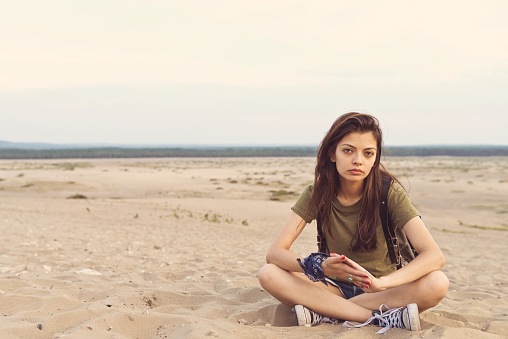 Portrait Of Bored Hiker Sitting On Sand In Desert Stock Photo - Download Image Now