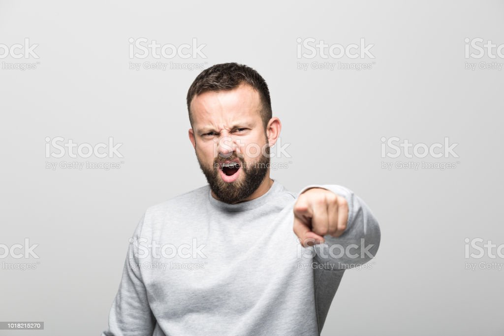 Portrait of bossy bearded young man pointing at camera with index finger Angry bearded young man shouting and pointing at camera with index finger. Studio shot, grey background. 30-34 Years Stock Photo
