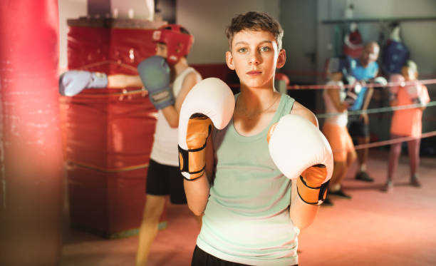 Portrait of  boy boxer wearing gloves at boxing hall stock photo