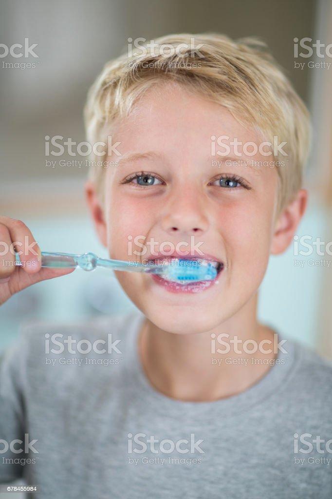 Portrait of boy brushing his teeth in bathroom royalty-free stock photo