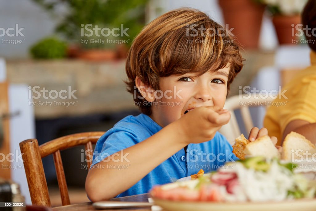 Portrait of boy eating food at table in house stock photo
