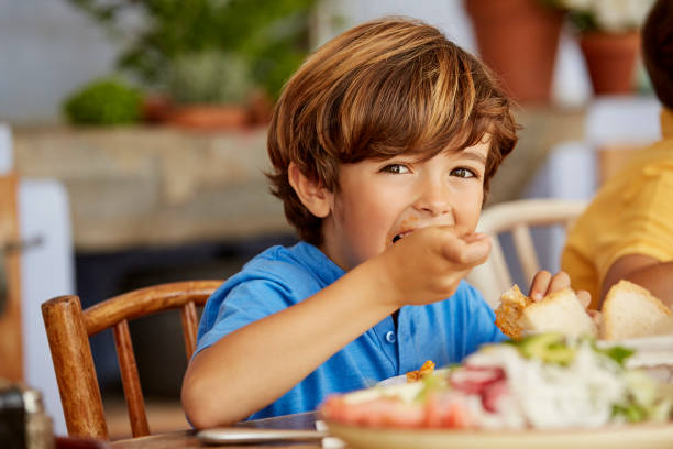 Portrait of boy eating food at table in house Portrait of boy eating food by table. Male is having lunch at home. He is wearing blue t-shirt. one boy only stock pictures, royalty-free photos & images