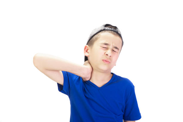 Portrait of boy having neck pain rubbing his neck over white background