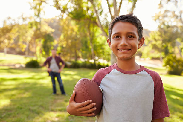 Portrait of boy holding football in park, dad in background stock photo