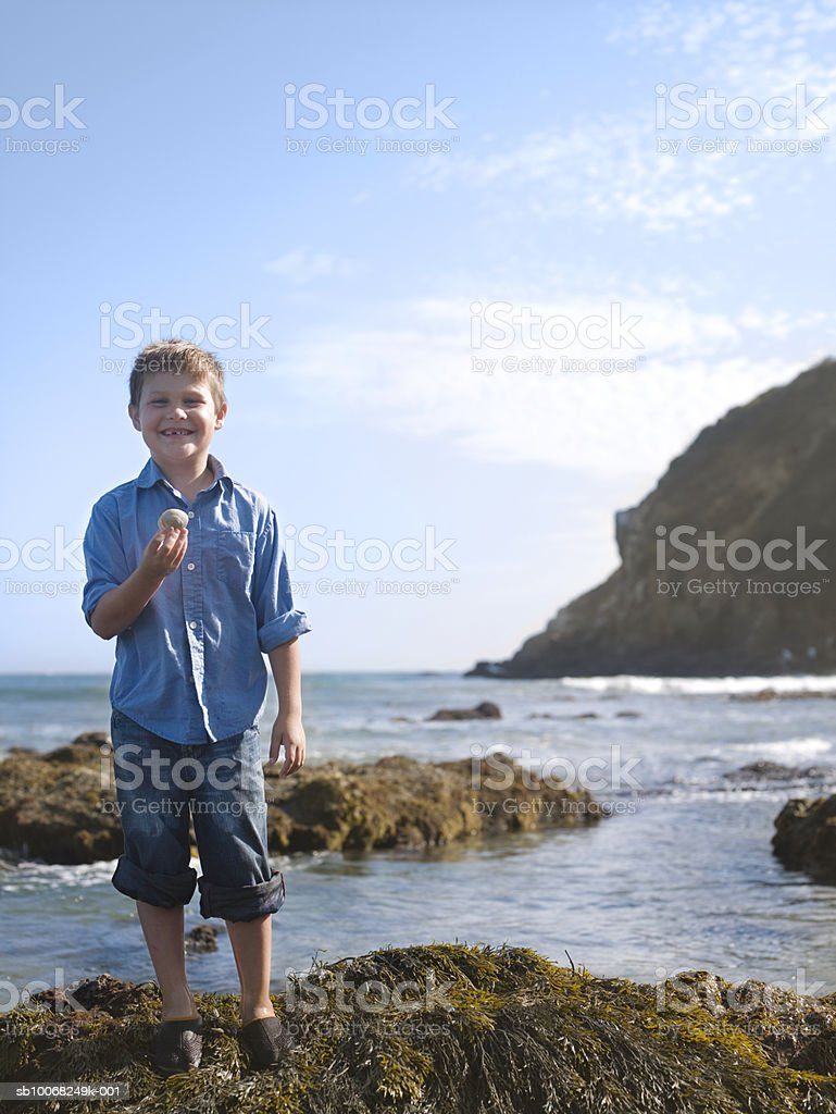Portrait of boy (6-7) holding shell at seashore royalty-free stock photo