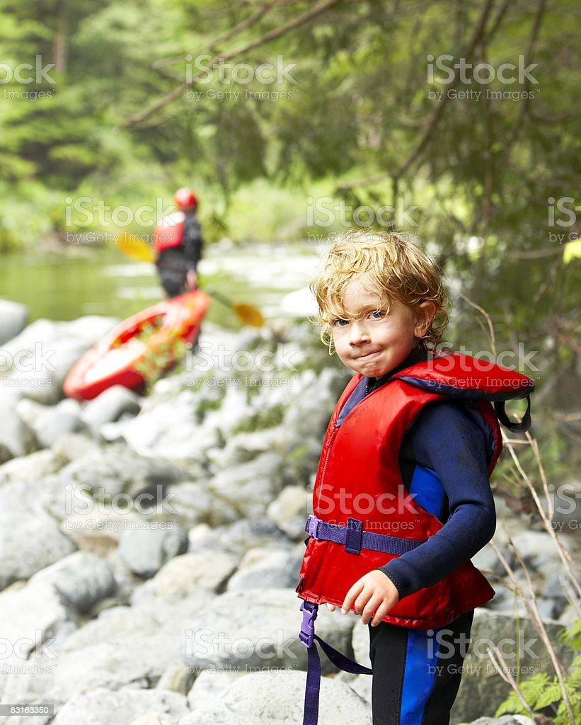 Portret chłopca w life preserver na brzeg rzeki. zbiór zdjęć royalty-free