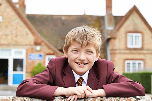 portrait of boy in uniform outside school building - private school stock photos and pictures