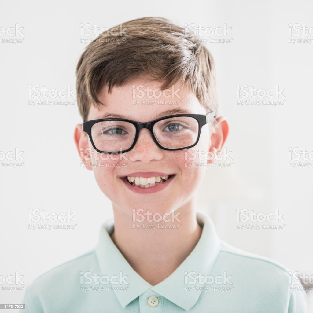 Portrait of boy looking at camera and smiling with glasses stock photo