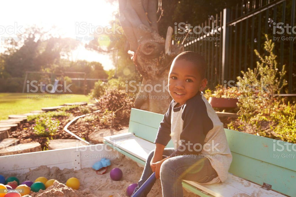 Portrait Of Boy Playing In Sand Box Outdoors In Garden stock photo