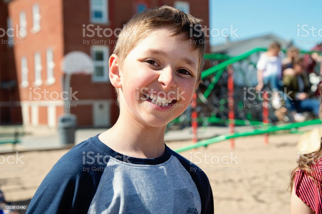 Portrait of boy playing in school playground at recess.. stock photo