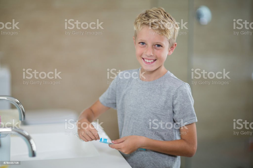Portrait of boy putting toothpaste on brush in bathroom royalty-free stock photo
