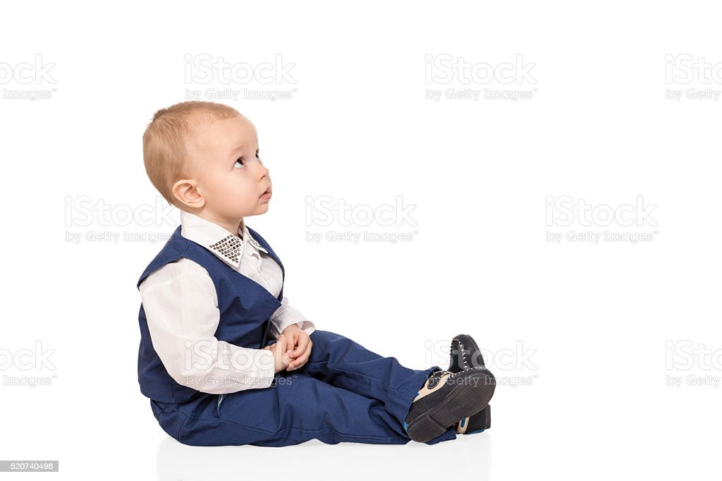 Portrait of boy sitting and looking up stock photo