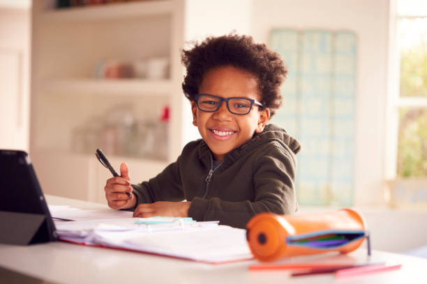 Portrait Of Boy Sitting At Kitchen Counter Doing Homework Using Digital Tablet stock photo