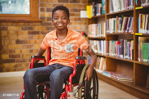 istock Portrait of boy sitting in wheelchair at library 474967218