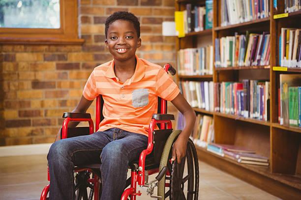 ritratto di bambino seduto in una sedia a rotelle alla biblioteca - sedia a rotelle foto e immagini stock