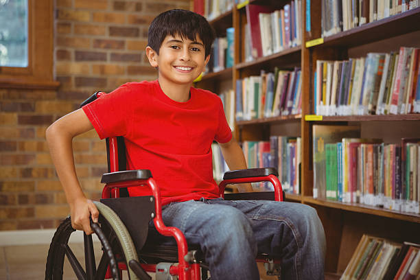 Portrait of boy sitting in wheelchair at library stock photo