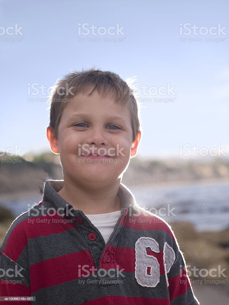 Portrait of boy (6-7) smiling at beach, backlit royalty free stockfoto
