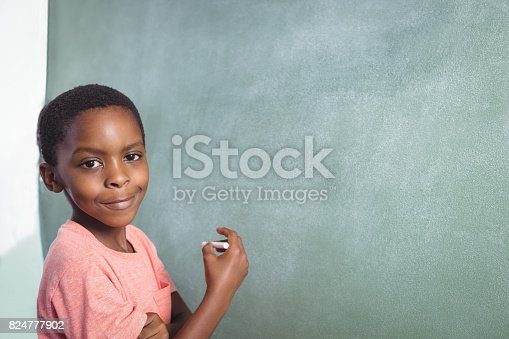 istock Portrait of boy standing by greenboard 824777902