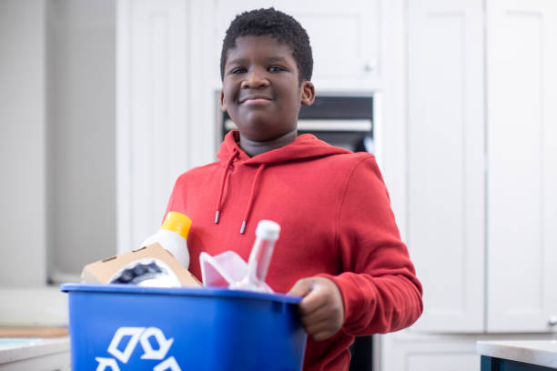 Portrait Of Boy Standing In Kitchen At Home Carrying Recycling Bin Portrait Of Boy Standing In Kitchen At Home Carrying Recycling Bin chores stock pictures, royalty-free photos & images