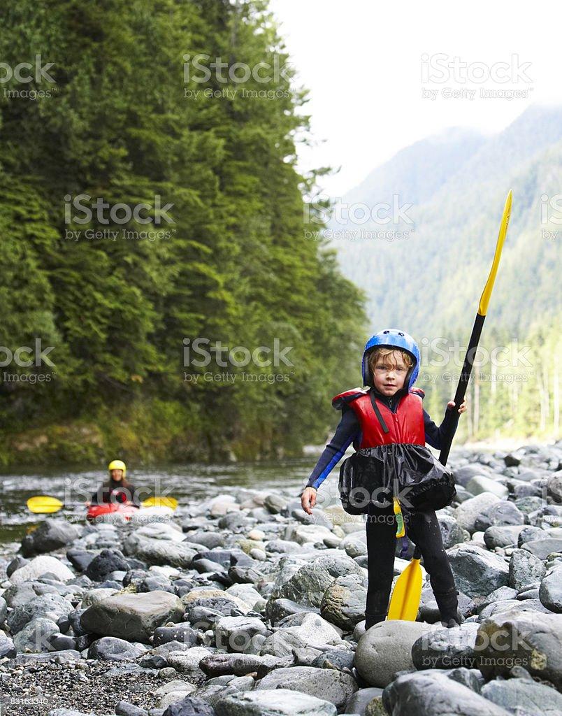 Portrait of boy wearing kayak gear holding paddle. royaltyfri bildbanksbilder