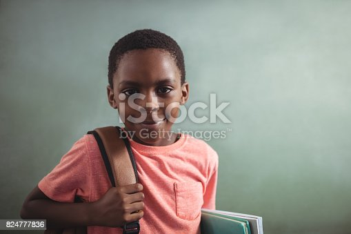 istock Portrait of boy with backpack and books against greenboard 824777836