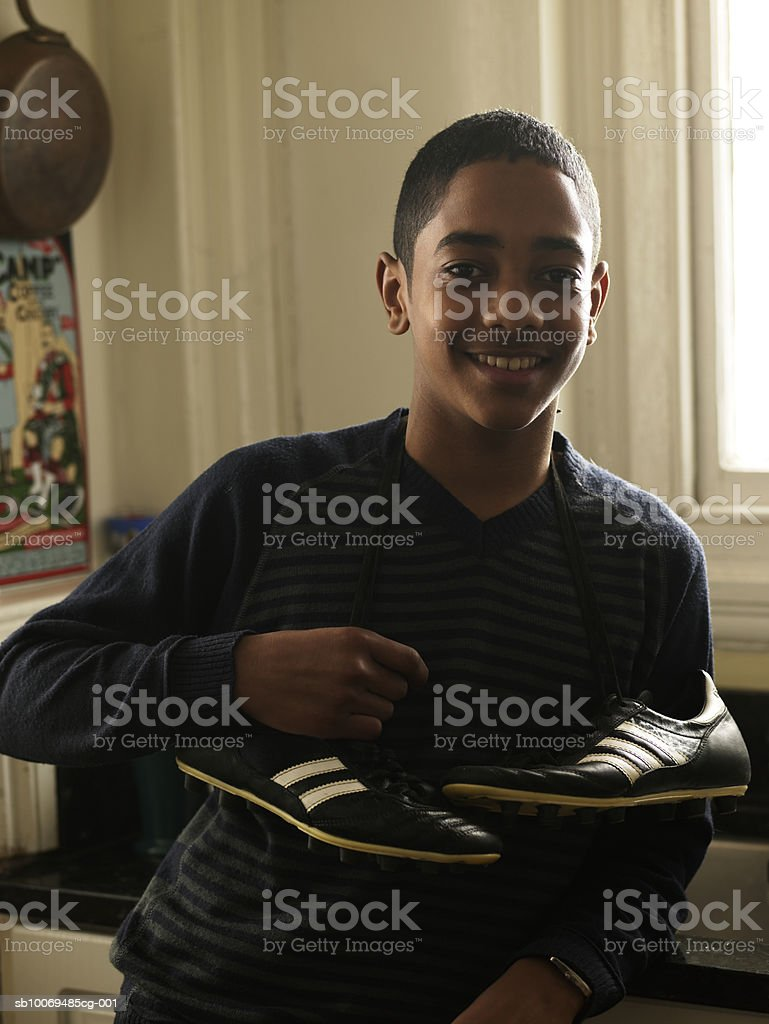 Portrait of boy (12-13) with sport shoes at home royalty-free stock photo