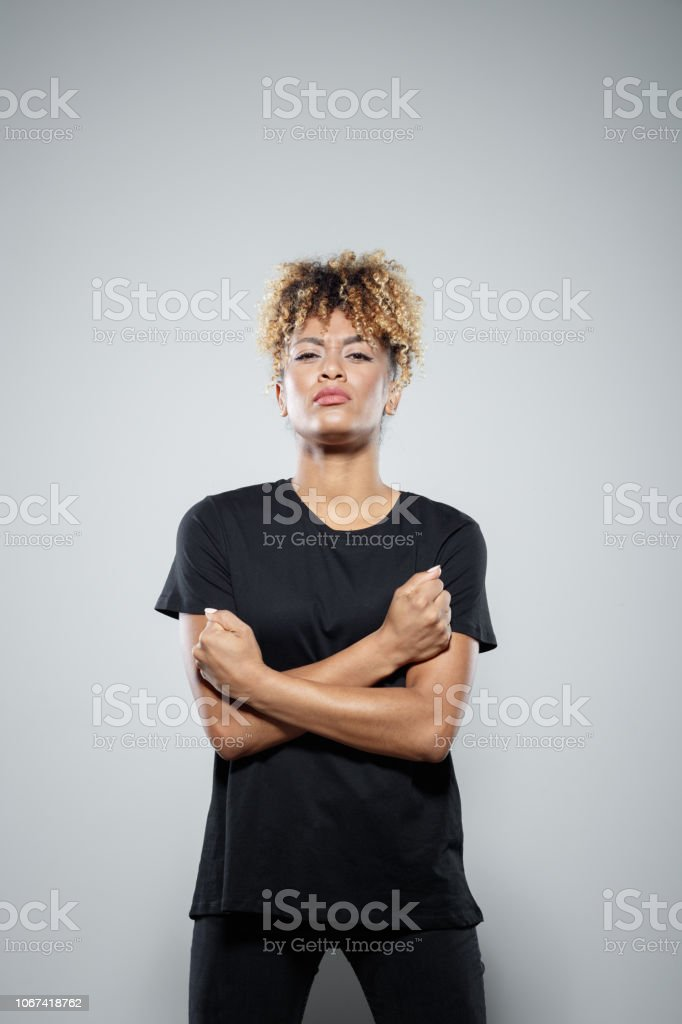 Portrait of brave young woman Strong young woman wearing black clothes, standing with arms crossed against grey background, staring at camera, clenching fists. Studio shot. Activist Stock Photo