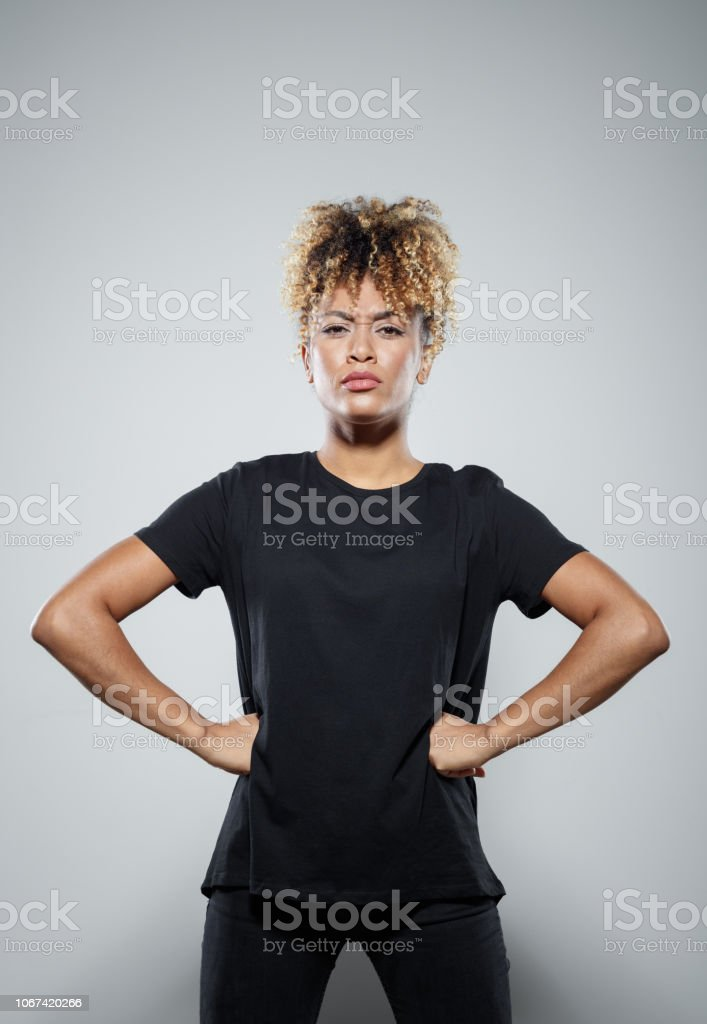 Portrait of brave young woman Strong young woman wearing black clothes, standing against grey background, staring at camera, clenching fists. Studio shot. Activist Stock Photo