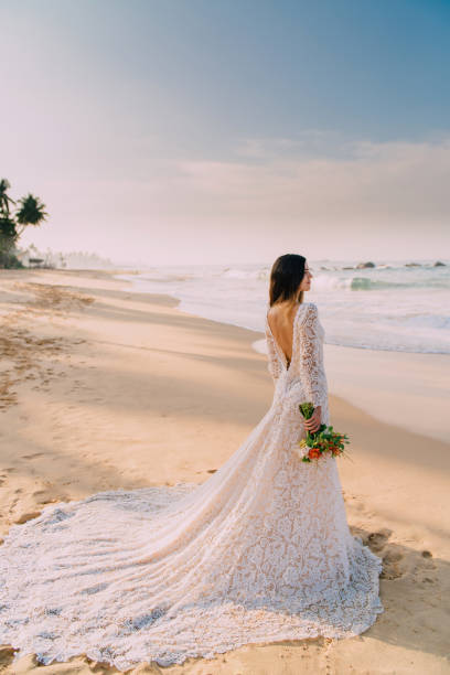 portrait of bride in full growth on tropical beach stock photo