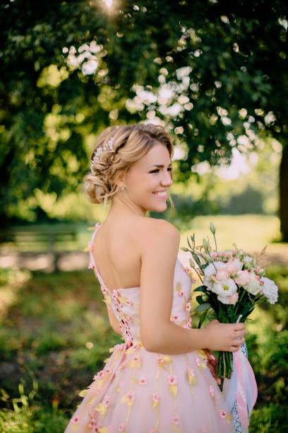 portrait of bride in pink dress stock photo