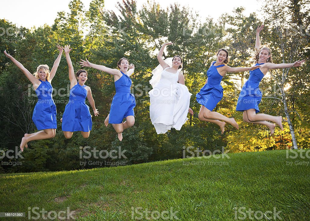 Portrait Of Bridesmaid And Bride Jumping stock photo