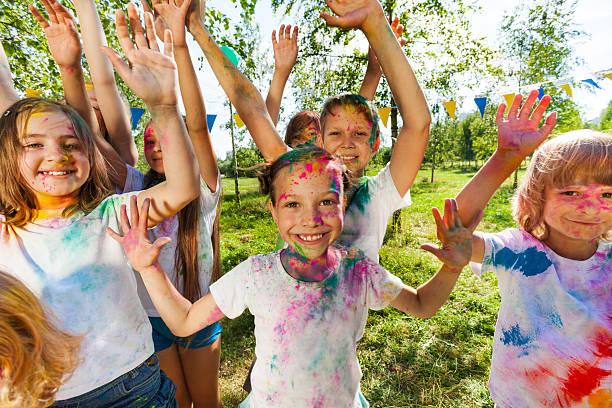 portrait of bright kids smeared in colored powder - kinderparty spiele stock-fotos und bilder