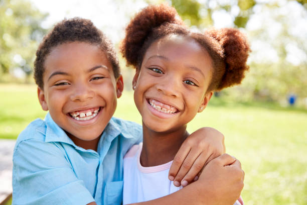 Portrait Of Brother And Sister Relaxing In Park Together Portrait Of Brother And Sister Relaxing In Park Together brother stock pictures, royalty-free photos & images