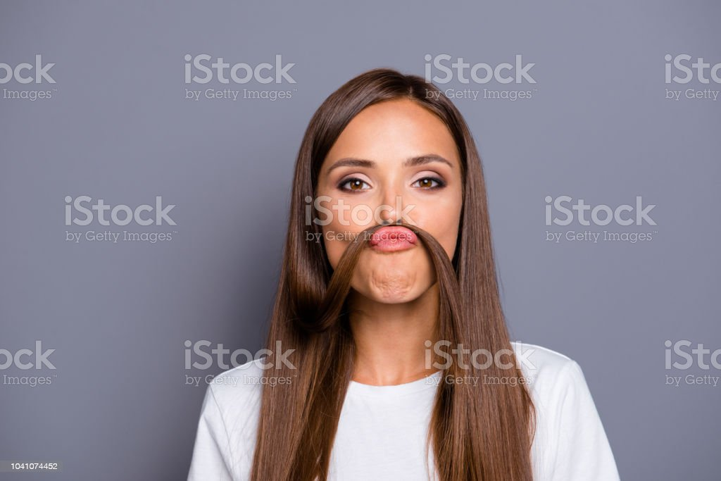 Retrato de morena linda jovem simpática fazer caretas com curl, bigode falso sobre fundo cinzento, isolado - foto de acervo