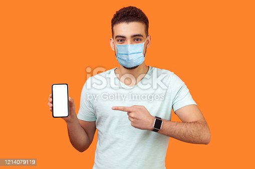 istock Portrait of brunette man with medical mask in white t-shirt pointing at cellphone and smiling at camera, recommending gadget or mobile application. 1214079119