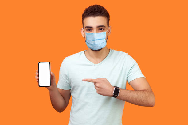 Portrait of brunette man with medical mask in white t-shirt pointing at cellphone and smiling at camera, recommending gadget or mobile application. stock photo