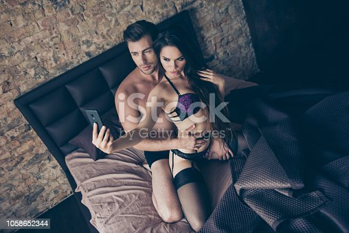 istock Portrait of  brunette woman with long hair and handsome sporty muscular masculine man taking selfie on telephone in bed 1058652344
