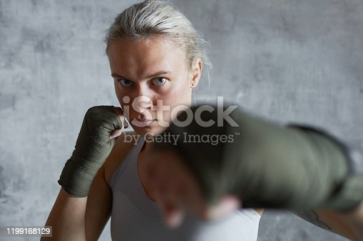 Portrait of brutal professional female boxer doing jab punch looking at camera
