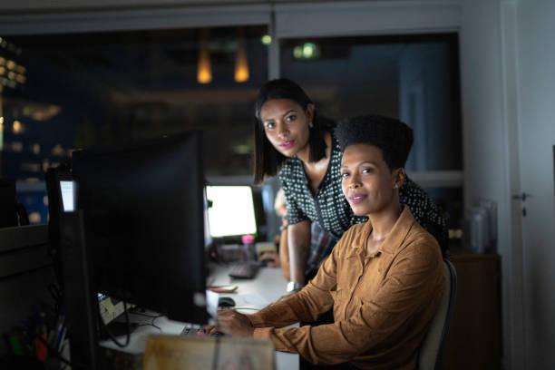 portrait of business partners working late in the office - persona in secondo piano foto e immagini stock