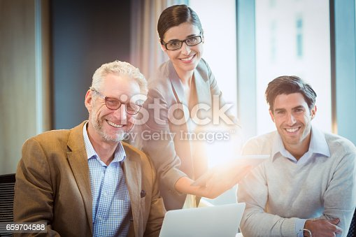 istock Portrait of business people discussing over digital tablet 659704588